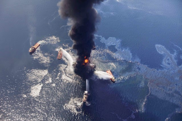 In this Wednesday, April 21, 2010 aerial file photo taken in the Gulf of Mexico more than 50 miles southeast of Venice on Louisiana's tip, an oil slick is seen as the Deepwater Horizon oil rig burns. (Credit: AP Photo/Gerald Herbert, file) Click to Enlarge.