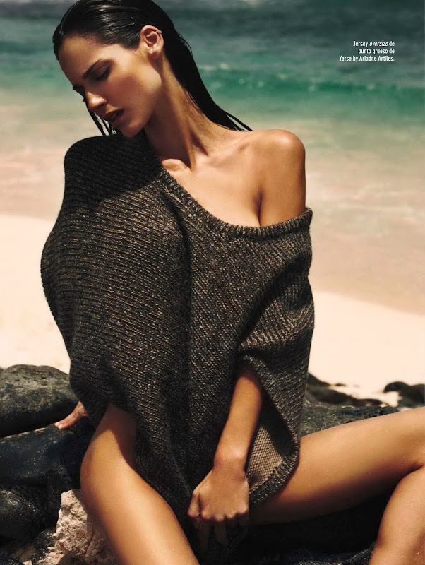 Ariadne Artiles covered with a sweater and sitting on the rocks