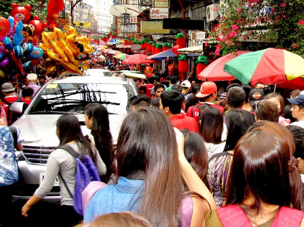 CHINATOWN: A car tries to pass through a thick crowd along Ongpin St.