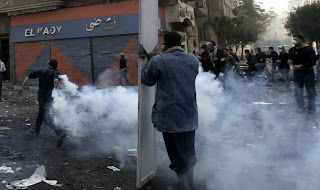 An Egyptian protester takes cover behind a shield
