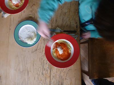 Draufsicht: Kind streut Parmesankäse auf seine Spaghetti