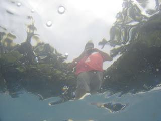 Foto feita de dentro da água mostrando uma pessoa do lado de fora.