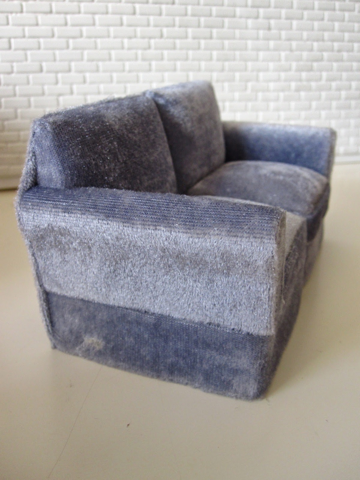 Modern miniature two seater grey velvet sofa.