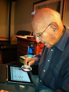 funny picture: grandpa using magnifying glass for ipad