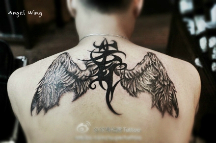 an angel wing tattoo with totem in between