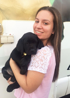 Jaclyn smiles holding a black Lab puppy in front of the Puppy Truck.