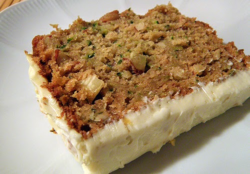 Frosted Zucchini Cake Floating on White Plate