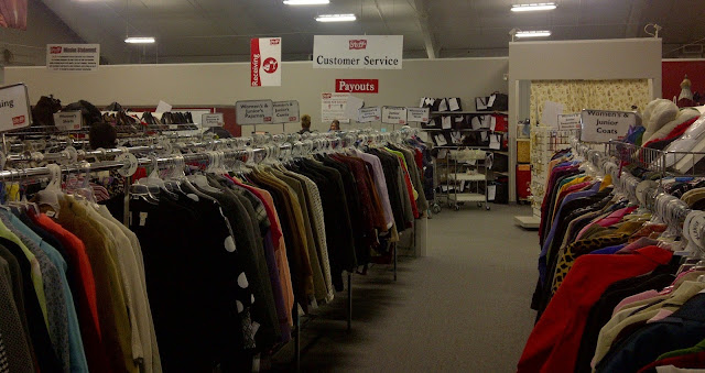 Racks of clothes for sale, payout desk in background