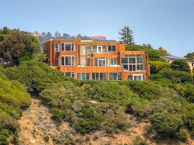Photo of house on the hill with surrounding vegetation