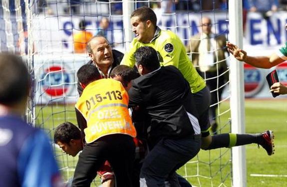 Bursaspor goalkeeper Harun Tekin attempts to kick a fan who invades the field