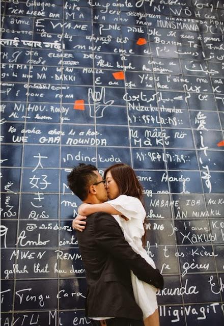 Couple d'amoureux devant le mur des je t'aime