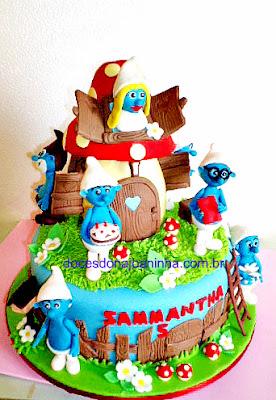 Bolo decorado Smurfs com casinha cogumelo e vários personagens Smurfs.