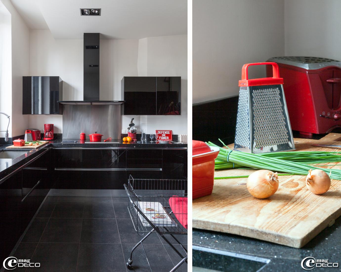 La cuisine de la maison d'hôtes 'La Villa 1901', à Nancy, équipée d'éléments noirs et métal brossé sur fond de blanc avec des objets et ustensiles de couleur rouge. Cocotte en fonte 'Nomar' de 'Paul Bocuse', grille pain et cafetière 'Rowenta', presse agrumes 'Riviera et bar'