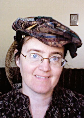 Cynthia Parkhill wearing a Tudor flat-cap. The crown is pieced together from brown and green diamond-shaped pieces of fabric. The brim is brown brocade on the outside and lined with dark green. A pheasant feather is pinned to the hat on the wearer's right and drapes to the back.