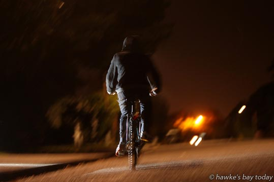 Posed pic of a cyclist without lights, helmet or hi-viz jacket, riding at night, in Hastings photograph