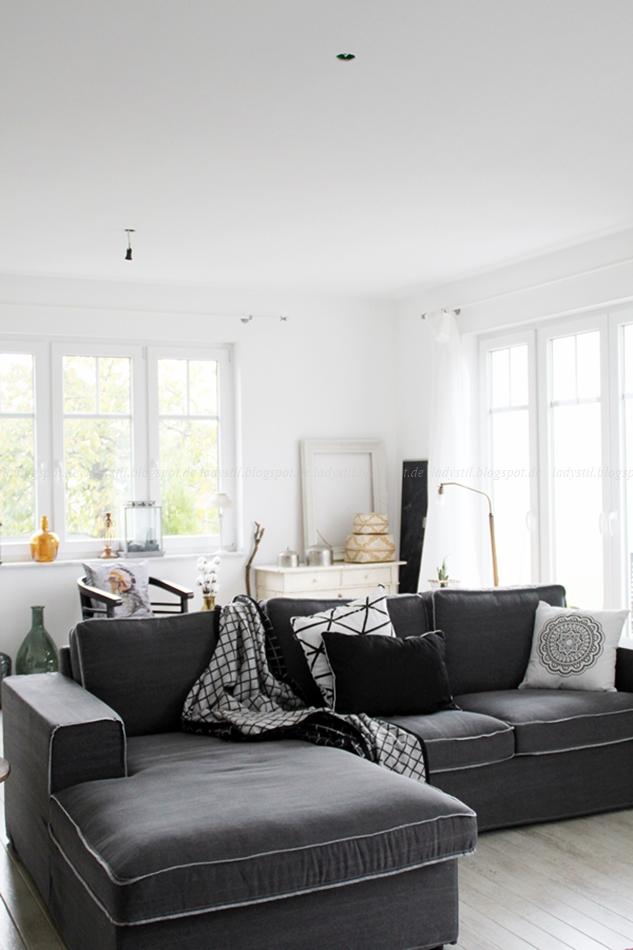 Gesamteindruck des Wohnzimmers Blick auf das Sofa, Kommode und diverse Wohnaccessoires