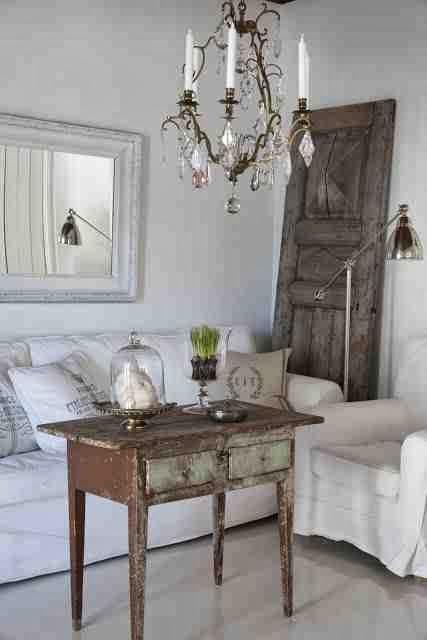 Wnętrze vintage, rustykalne dekoracje, biała sofa, metalowa lampa stjąca, stare drzwi oparte o ścianę, drewniany stolik