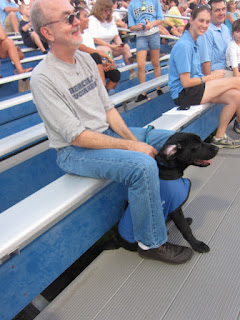 Fred with Coach sitting between his legs on the bleachers.  Coach has one ear laid back.