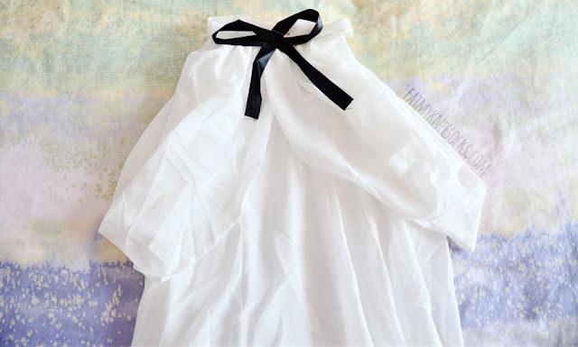 Close-up of Dresslink's black and white ribboned off-shoulder blouse.