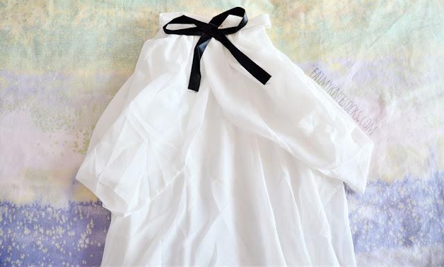 Close-up of Dresslink's black and white ribboned off-shoulder blouse.