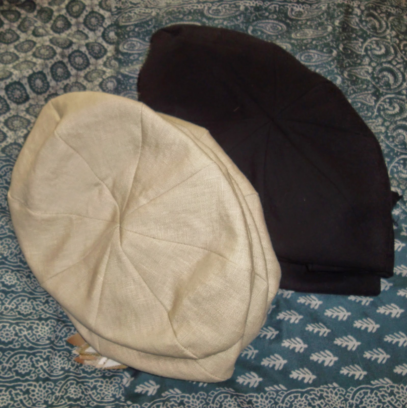 The crowns of newsboy-style, eight-paneled hats are stacked in piles of solid off-white and black hats.
