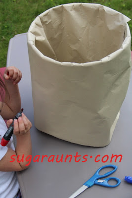 craft paper wrapped and taped around five gallon bucket