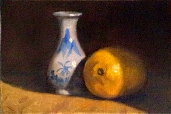 Oil painting of an onion-shaped blue and white miniature vase beside a lemon.