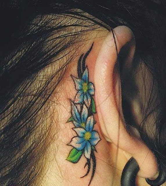Beautiful and small flower tattoo on back side of ear