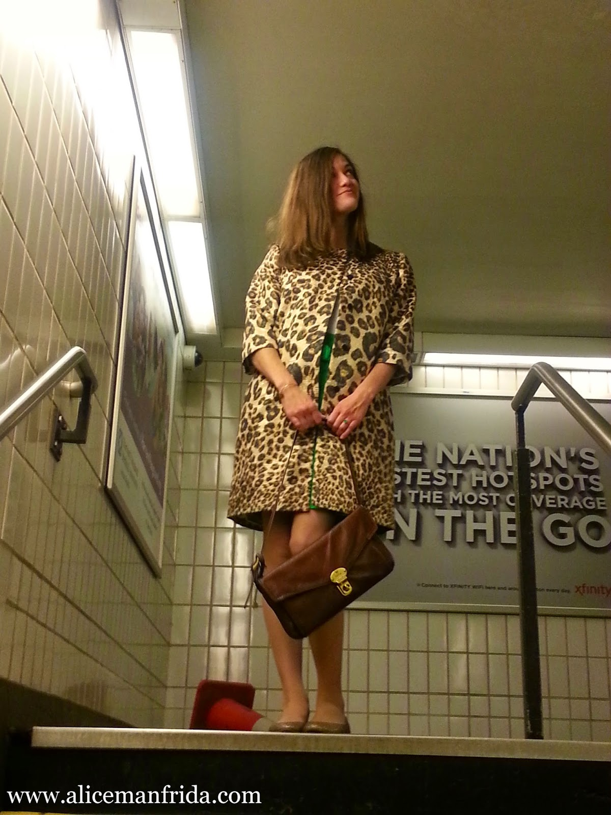 A woman standing in a subway station wearing a leopard statement coat and holding a brown leather handbag from Fossil