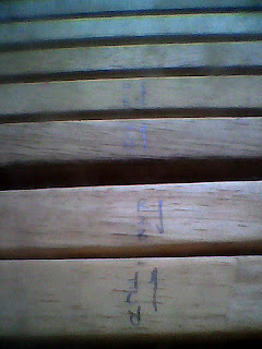 The twelve slats from the futon frame are marked for layout and assembly.