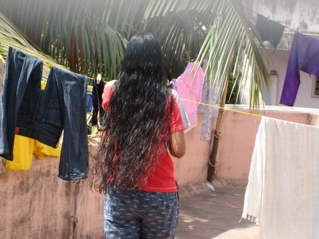 long hair lady  washing and drying her clothes.