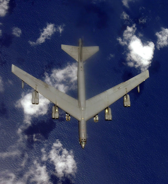 B-52 Stratofortress over sea top view with bombs.