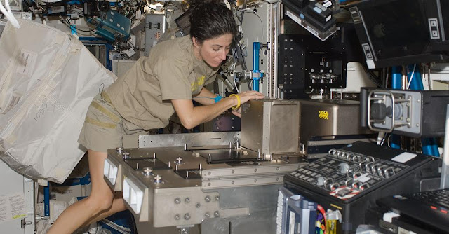 NASA astronaut Nicole Stott, Expedition 21 flight engineer, installs hardware in the Fluids Integrated Rack (FIR) in the Destiny laboratory of the International Space Station in October 2009. Credit: NASA