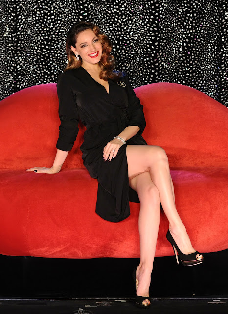 Kelly Brook in black dress sitting on the red chair