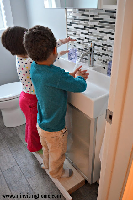 two kids washing their hands at the same time