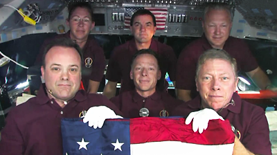 Atlantis – STS135 – The crew of Atlantis took an American flag to the ISS, which will be returning to its home at Miami Dade Police department. NASA-TV 2011.