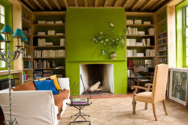 Living room with chartreuse painted fireplace, chartreuse trimmed windows, the back of the bookcases surrounding the fireplace are also painted chartreuse. The room has a white sofa, neutral area rug and wooden, and a upholstered high back chair