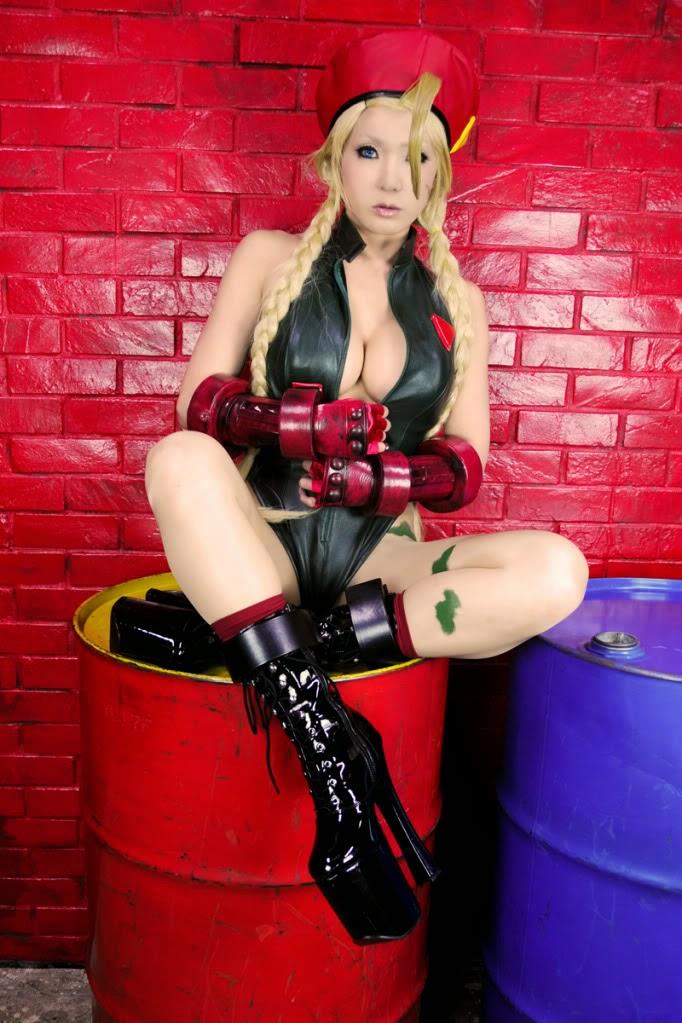 cosplay féminin très sexy d'une combattante de dead or alive assise sur un bidon avec des talons hauts