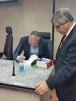 Dr. Ricardo autografando um livro para o vice-diretor  da EMERJ, Desembargador Paulo Baldez,