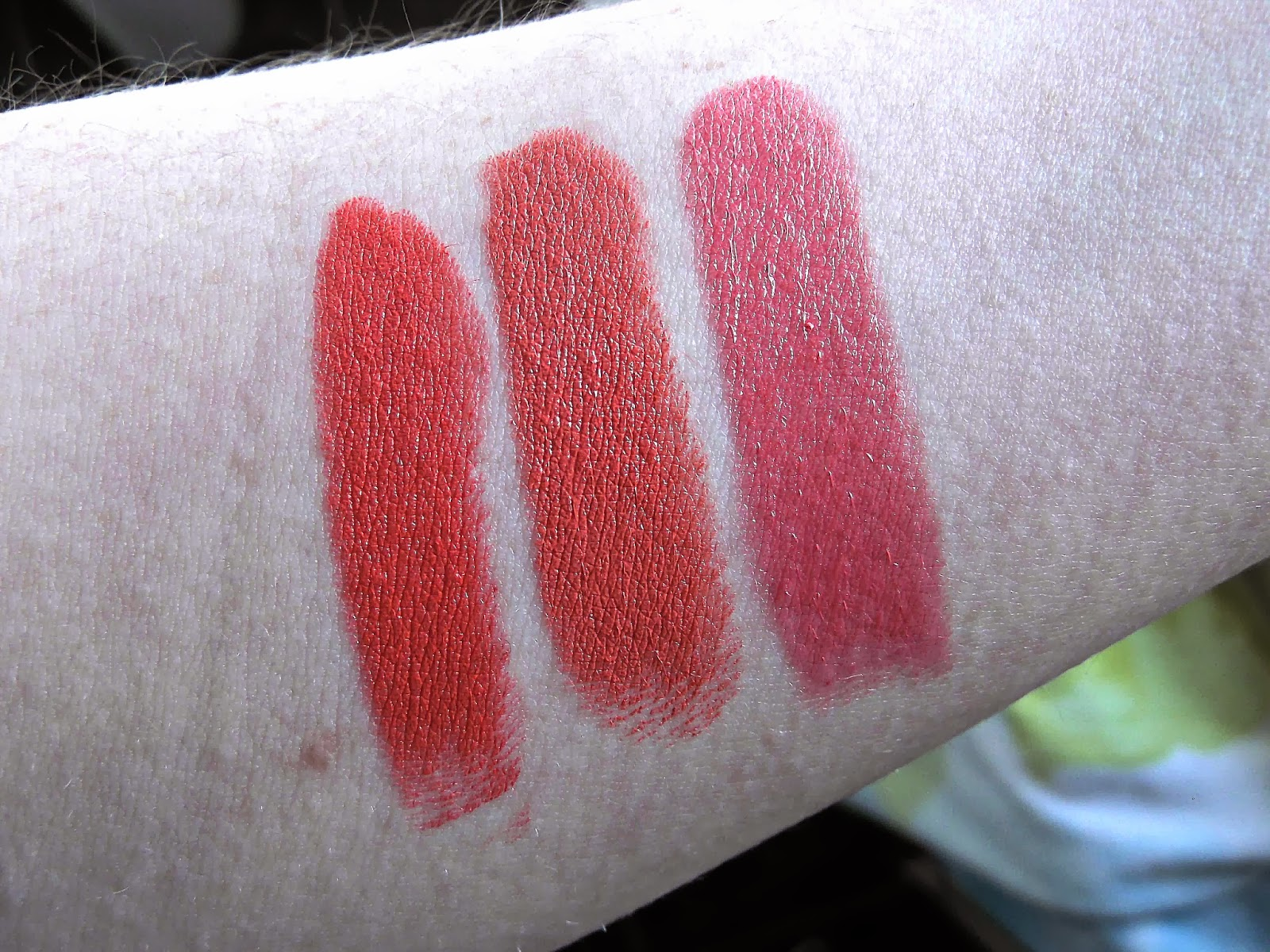 An Image of Swatches of MAC Amplified Lipstick in Vegas Volt, Barry M Lip Paint in 151 Sunset and Benefit Lipstick in My Treat