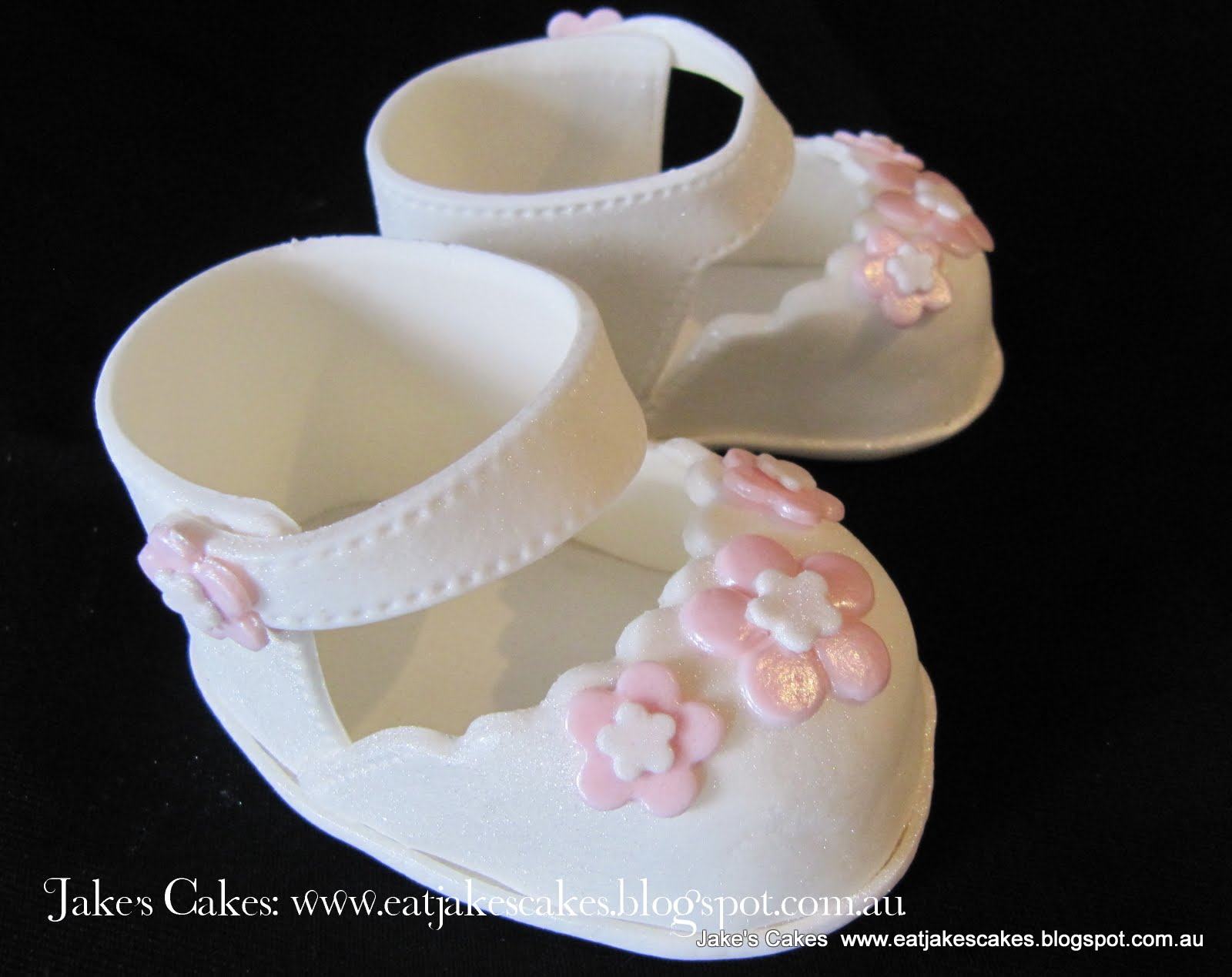 Fondant Cross And Baby Shoes On A Cake