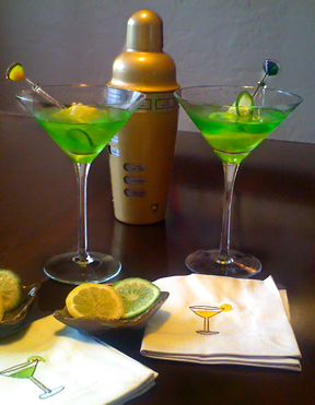 Midori Illusion cocktails, in martini glasses and garnisher with a lemon and a lime slice. Drink shaker in the background