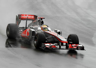 Lewis Hamilton driving around a wet Circuit