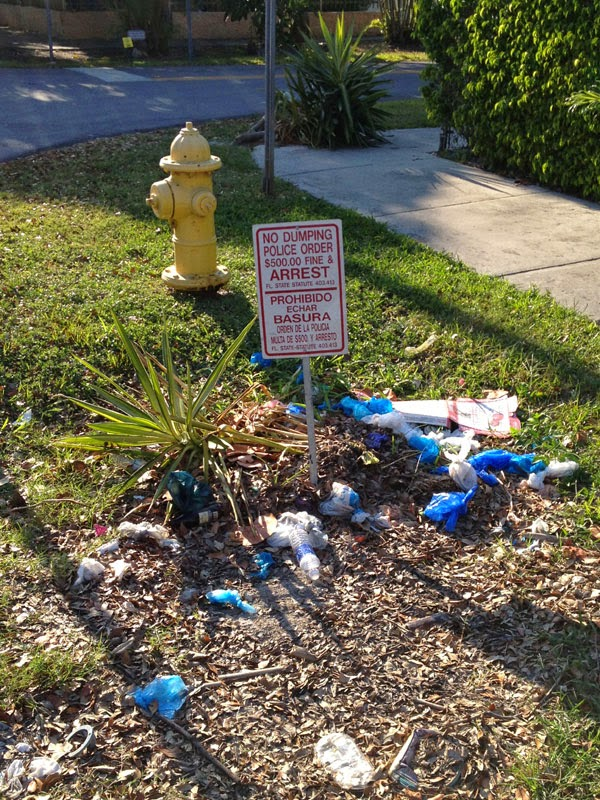 Curbside trash pit in Coconut Grove (Note English/Spanish warning sign)