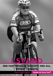 "Black and white photo of the author, a fat woman wearing black cycling shorts, a jersey that says ""Erik's"", a helmet, sunglasses, and a ponytail.  Bike is a road bike with thin tires and close curved handles.  Text reads ""I STAND for fun physical activity for all. Weight =/= health"""