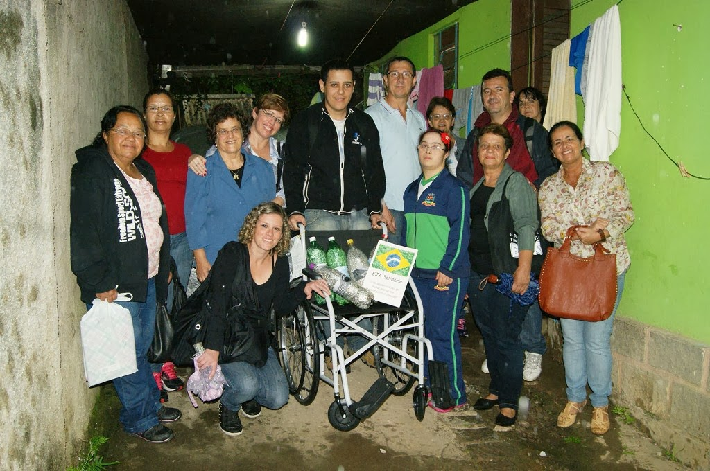 Alunos e equipe da EJA posam com a primeira cadeira de rodas trocada e as garrafas cheias de lacres para troca pela próxima cadeira