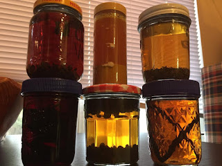 A selection of vodkas steeping in assorted jars. Here: Clove, turmeric, rosemary, hibiscus, juniper, vanilla.