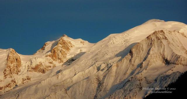 les montagnes du Mont-Blanc et du Mont-Maudit très enneigées et éclairées par le soleil couchant.