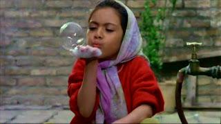 La pequeña sopla una burbuja.
