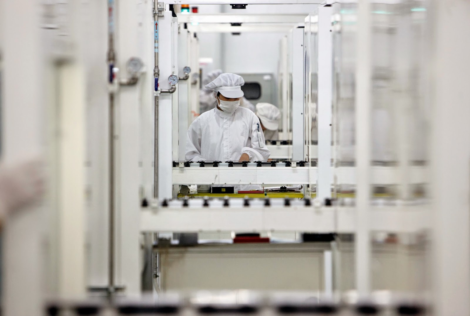 Workers operate on the assembly line that makes photovoltaic cells, the main energy generating component of a solar panel, at the Suntech Power Holdings Co. factory in Wuxi, China. (Credit: Qilai Shen/Bloomberg) Click to enlarge.